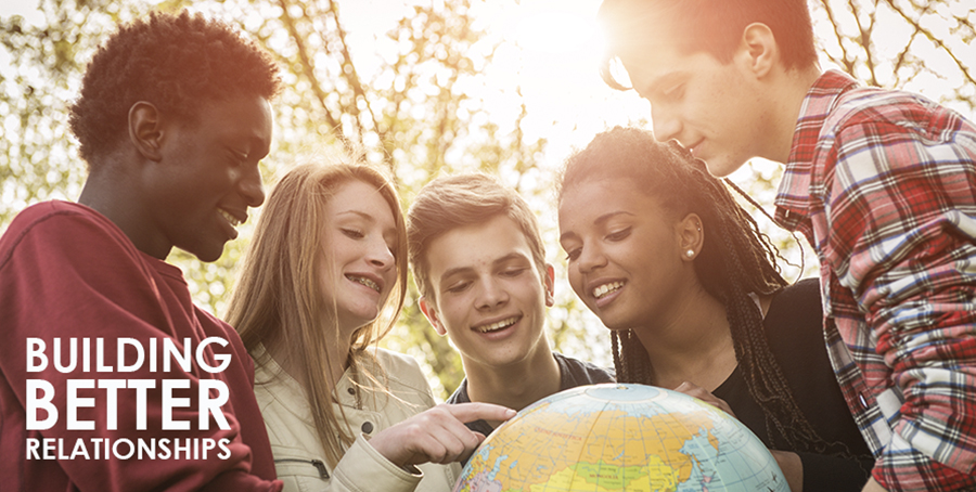 Teenagers exploring a globe of the world