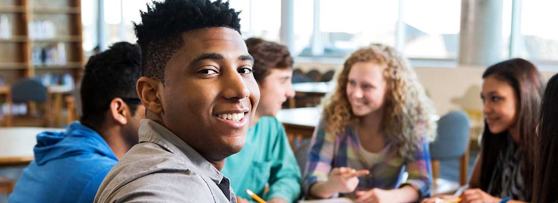 young man smiles confidently toward you away from group of students at a student meeting
